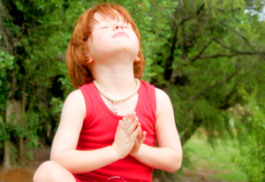 A child meditating in the forest